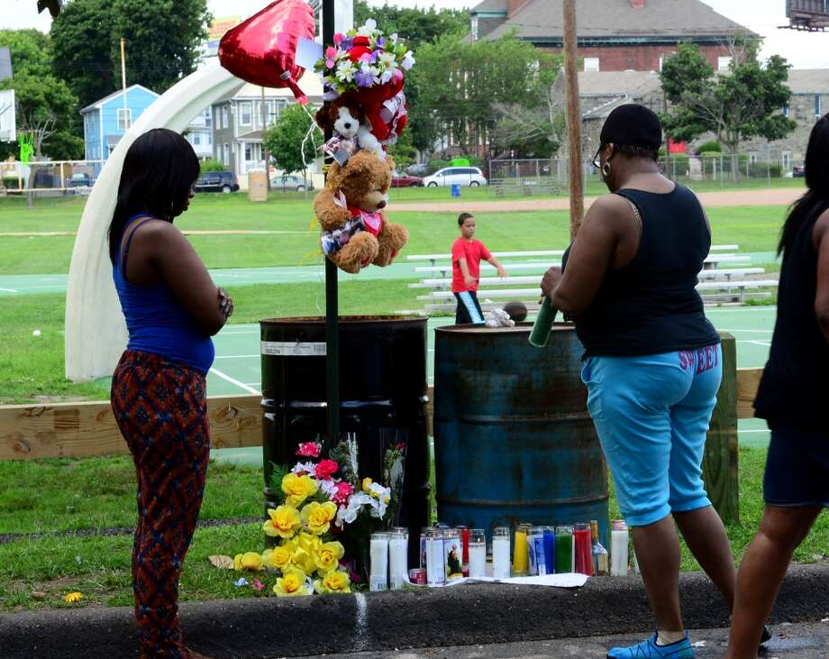 Friends of shooting victim Joseph Myers place candles and flowers at a memorial on Jefferson Street in Bridgeport, Conn. on Wednesday July 16, 2014. Myers was brutally shot in the back of his head Wednesday night while he sat in the back of his Honda Civic. Photo: Christian Abraham