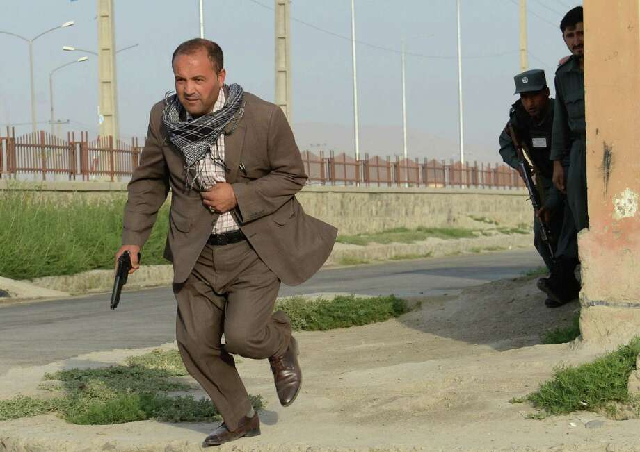 An Afghan security member runs for cover during the Taliban's attack on the airport in Kabul. Photo: Massoud Hossaini / Associated Press / AFP