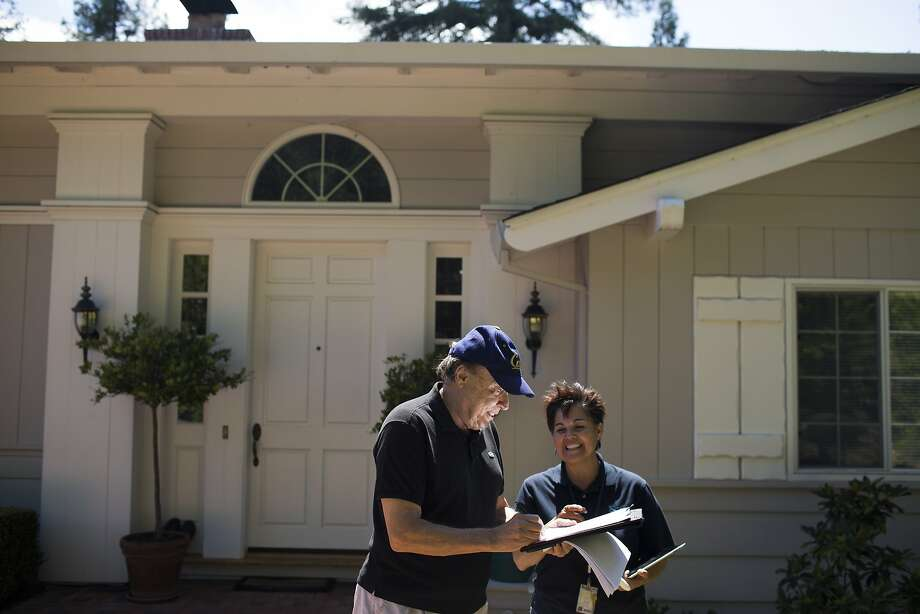 Rachel Garza, with the East Bay Municipal Utility District, discusses water use with an Orinda resident. Photo: Tim Hussin, Special To The Chronicle