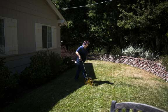 Rachel Garza, water conservation technician with East Bay Municipal Utility District, takes measurements of a EBMUD customer's lawn in Orinda, Calif. on Thursday, July 17, 2014. The customer chose to let his front lawn die in order to benefit from rebates on his water bill.