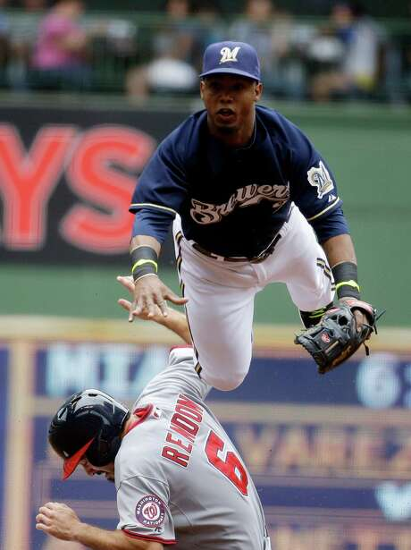 Milwaukee Brewers shortstop Jean Segura leaps over Washington Nationals' Anthony Rendon to try and turn a double play on a ball hit by Ian Desmond during the second inning of a baseball game Wednesday, June 25, 2014, in Milwaukee. Desmond beat the throw to first. (AP Photo/Morry Gash) Photo: Morry Gash, STF / AP