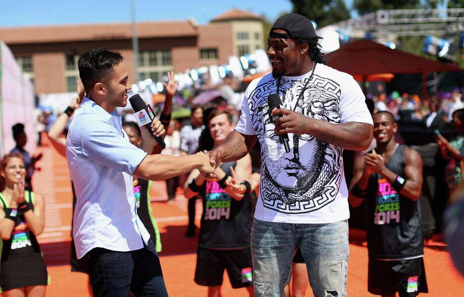 TV host Carlos PenaVega, left, with NFL player Marshawn Lynch  attends Nickelodeon Kids' Choice Sports Awards 2014 at UCLA's Pauley Pavilion on July 17, 2014 in Los Angeles, California. Photo: Mark Davis, Getty Images For Nickelodeon / 2014 Getty Images