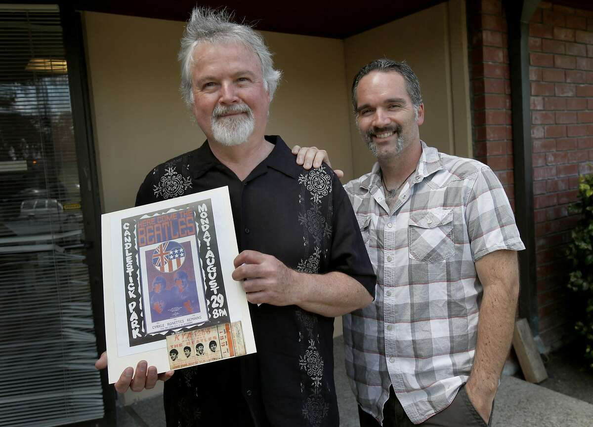Terry Dilbeck (left) holds his unused Beatles concert ticket and poster with his son Kris Dilbeck Tuesday July 15, 2014. Terry Dilbeck cherishes his ticket to the Beatles last concert at Candlestick Park, although he never attended. His best friend, and ride to the concert, got grounded at the last minute. He plans to take his son Kris to the last show at Candlestick in August.