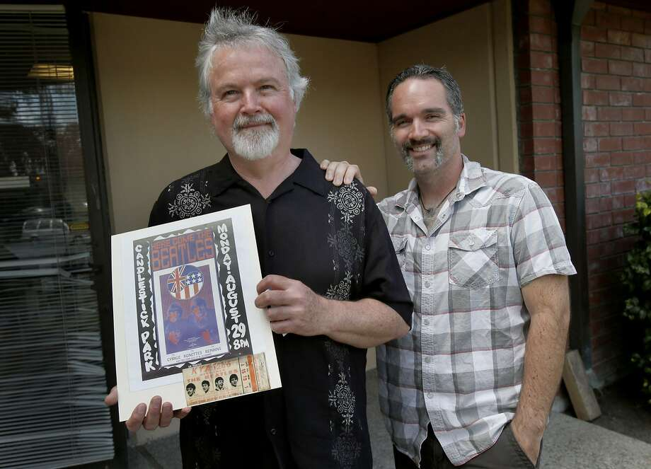 Terry Dilbeck, with son Kris, holds the poster and ticket - that he didn't use - to the Beatles' farewell concert at Candlestick. Photo: Brant Ward, San Francisco Chronicle