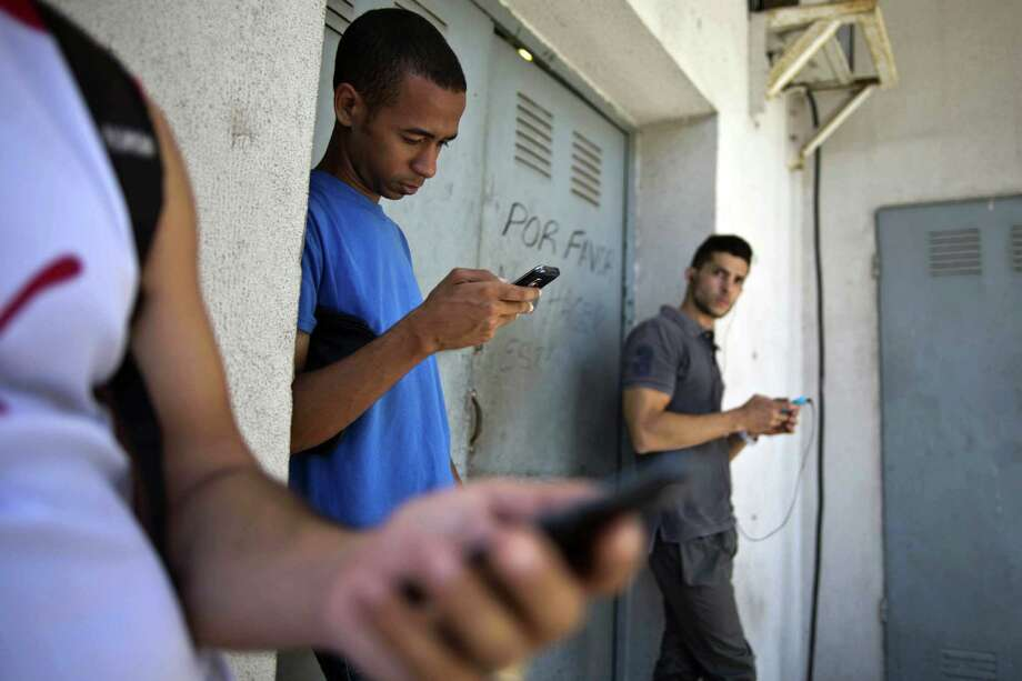 """Students look for an Internet signal and possibly the """"Cuban Twitter"""" in Cuba. Photo: Ramon Espinosa / Associated Press / AP"""