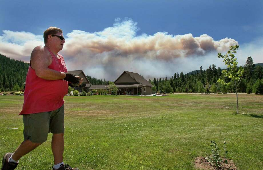 Bob Lamar works around his home in Plain, Washington, after getting an evacuation notice. He and his wife are waiting to see where the fire burns before deciding whether to leave. Photo: Don Seabrook / Wenatchee World / The Wenatchee World