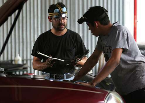 Edwuard Salgado Cabrera, right, who arrived in the U.S. back in May, 2014 from Honduras, listens to his cousin Juan Miguel Resendiz, owner of Resendiz Auto Repair. Resendiz is teaching the 16 year-old auto mechanics as he helps out at the auto shop on Nogalitos Rd. Cabrera and his mother are living at her cousin's house. They have a court date in January 2015 to determine their status.  Thursday, July 17, 2014. Photo: BOB OWEN, San Antonio Express-News / © 2012 San Antonio Express-News