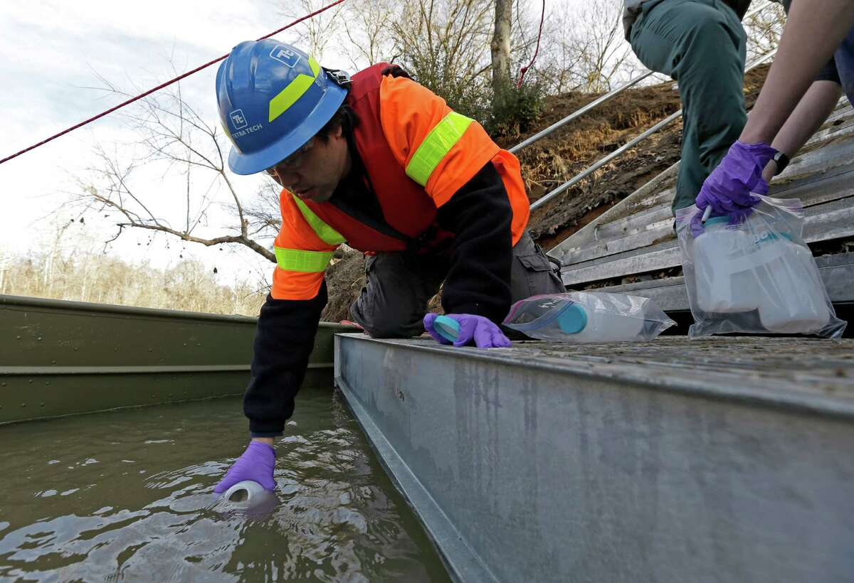 Didi Fung, a contractor for the Environmental Protection Agency, collects water samples from the Dan River after the spill in February.