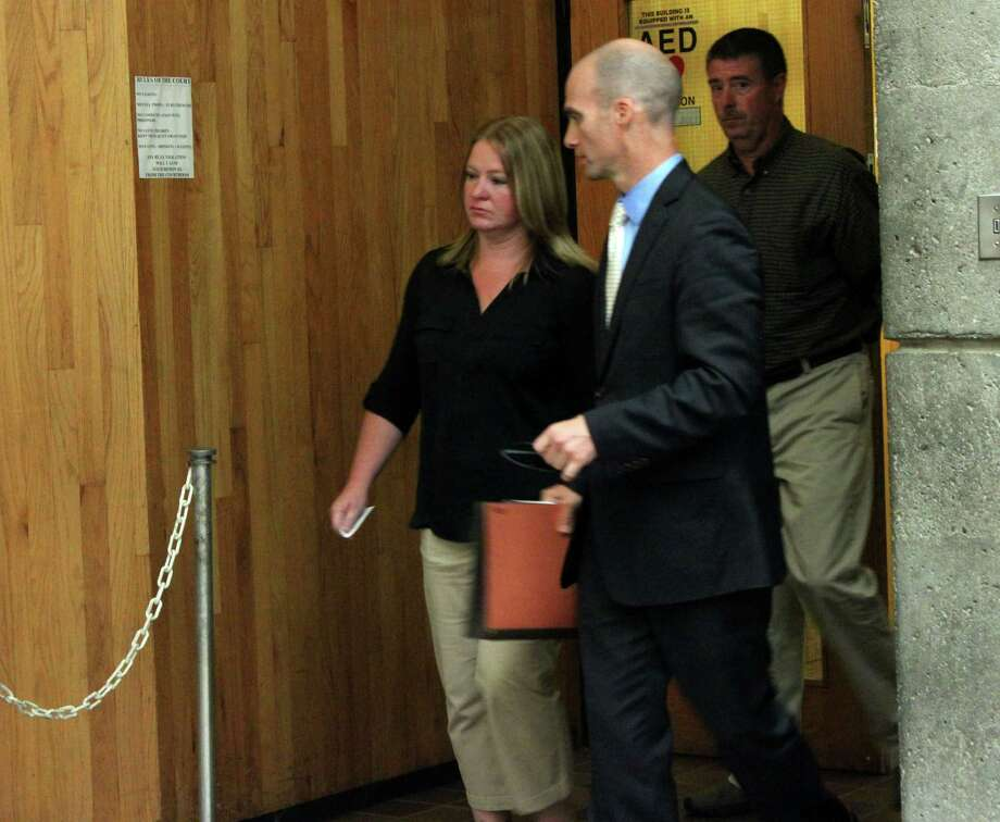 Carrie LaFond of Schenectady, left, is led out of the Schenectady courthouse by her attorney James Knox, right, and followed by her husband, Paul LaFond Thursday, July 17, 2014, in Schenectady, N.Y. Carrie was a trusted accountant at John D. Marcella & Son Appliances & Home Entertainment and surrendered to authorities Thursday to face accusations she embezzled from the company. (Selby Smith/Special to the Times Union)