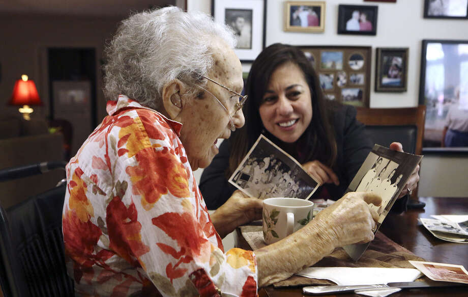 Women's Army Auxiliary Corps veteran Lucy Coffey, 108, and Queta Marquez, Bexar County veterans service officer, recently looked at pictures that were taken when Coffey was in Japan. Photo: Helen L. Montoya / San Antonio Express-News / SAN ANTONIO EXPRESS-NEWS