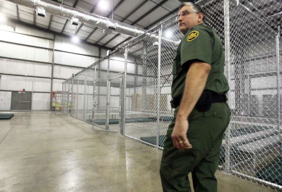 Border Patrol Agent Roel Rodriguez walks through empty holding cells at the new facility built to help alleviate overcrowding at the U.S. Customs and Border Protection's McAllen station. Photo: Joel Martinez / Associated Press / The McAllen Monitor
