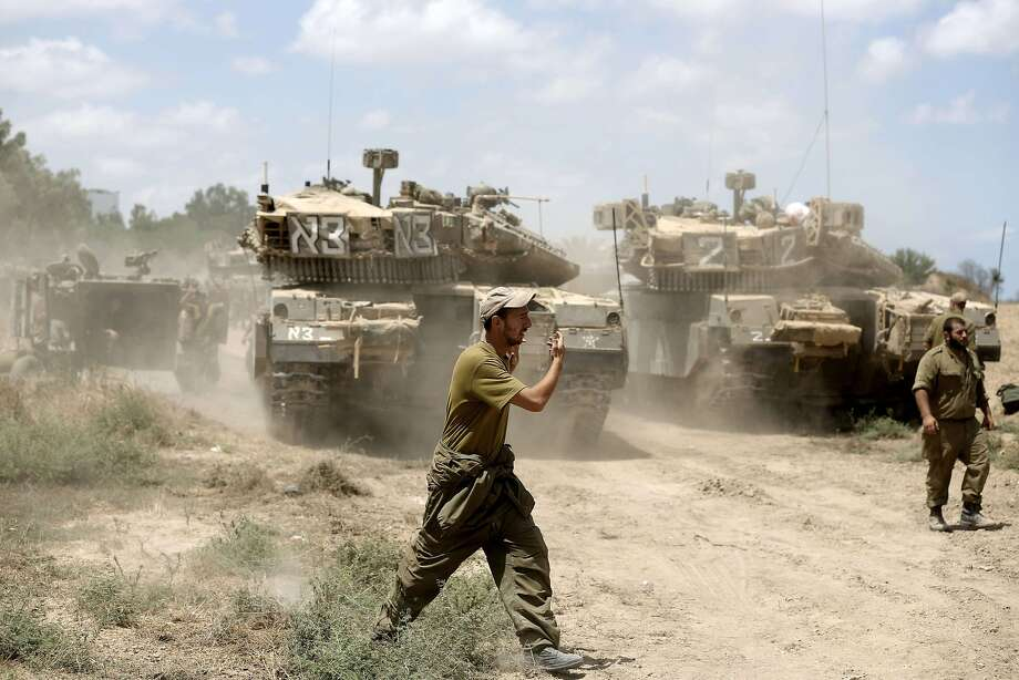An Israeli soldier directs a Merkava tank at an army deployment area near the border with Gaza. Photo: Menahem Kahana, AFP/Getty Images