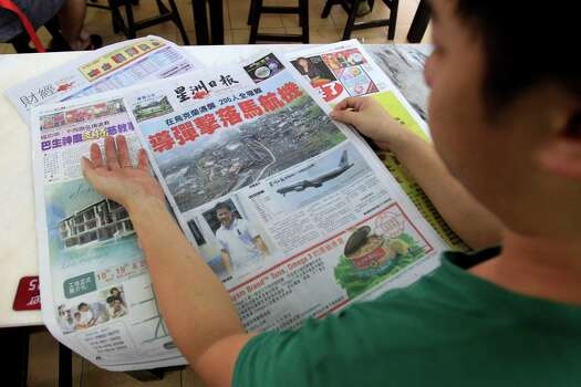 At a restaurant in Shah Alam, outside Kuala Lumpur, Malaysia, on Friday, July 18, 2014, aman reads a Chinese newspaper report on the crash. Photo: Lai Seng Sin, AP / AP