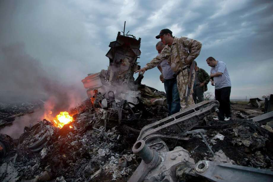 People inspect the crash site of a passenger plane near the village of Grabovo, Ukraine, Thursday, July 17, 2014. Ukraine said a passenger plane carrying 295 people was shot down Thursday as it flew over the country, and both the government and the pro-Russia separatists fighting in the region denied any responsibility for downing the plane. (AP Photo/Dmitry Lovetsky) ORG XMIT: MOSB110 Photo: Dmitry Lovetsky / AP2014