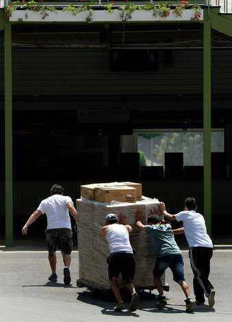 Workers move supplies in to the grandstand area Thursday morning, July 17, 2014, at Saratoga Race Course in Saratoga Springs, N.Y.  (Skip Dickstein / Times Union) Photo: SKIP DICKSTEIN / 00027702A