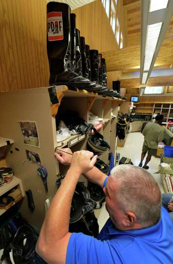 Valet Harry Rice gets his jockey's possessions ready for opening day Thursday morning, July 17, 2014