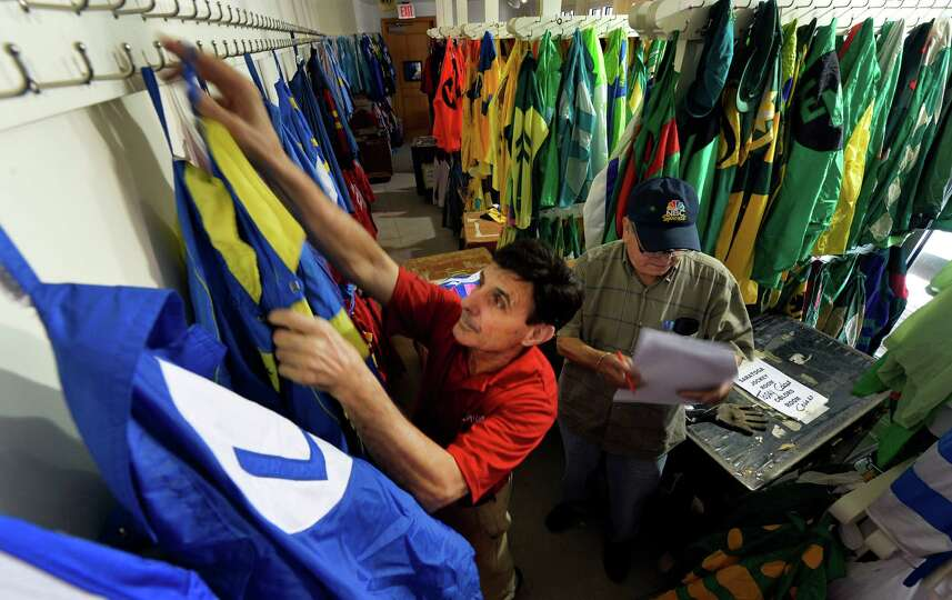 Colors workers Frank Lopez, left and Walter Arce put out the silks for opening day Thursday morning,