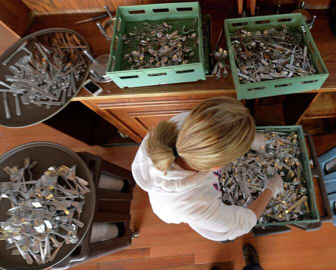 Server Maria Zambrano sorts silverware in the dining area on the first floor of the Clubhouse Thursd