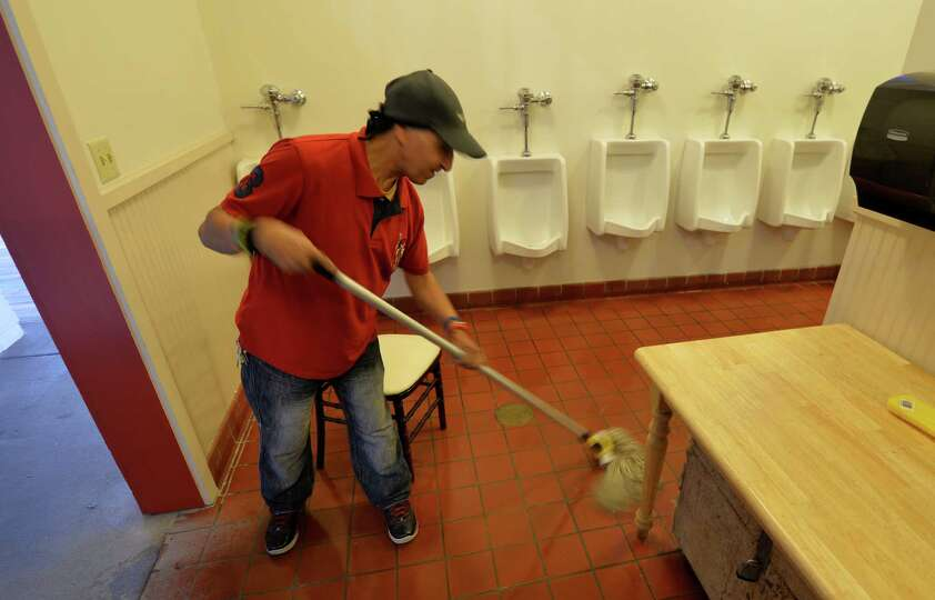Jorge Santana puts the finishing touches as he cleans the floors in the restroom Thursday morning, J
