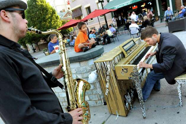 Lecco Morris on piano, right, and Jeff Nania on saxophone, both of the Electric City Washtub Trio, play jazz as part of the Piano Project in front of McGeary's on Thursday, July 17, 2014, in Albany, N.Y. Xavier Bing, 7, of Albany, center, drums along. (Cindy Schultz / Times Union) Photo: Cindy Schultz / 00027827A
