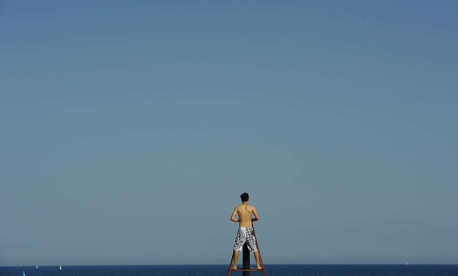 A man looks out to sea, at the beach, in Barcelona, Spain, Thursday, July 17, 2014. Most of Spain is experiencing a heat wave with temperatures reaching around 40 degrees Celsius (104 degrees Fahrenheit). (AP Photo/Manu Fernandez) Photo: Manu Fernandez, Associated Press