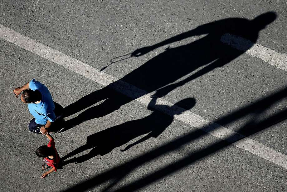 The shadows of a Palestinian father and son are seen in a street in Gaza City on July 17, 2014. Israeli air strikes in Gaza killed four children, medics said, after a humanitarian lull in a 10-day conflict that has killed 237 Palestinians. AFP PHOTO / THOMAS COEXTHOMAS COEX/AFP/Getty Images Photo: Thomas Coex, AFP/Getty Images