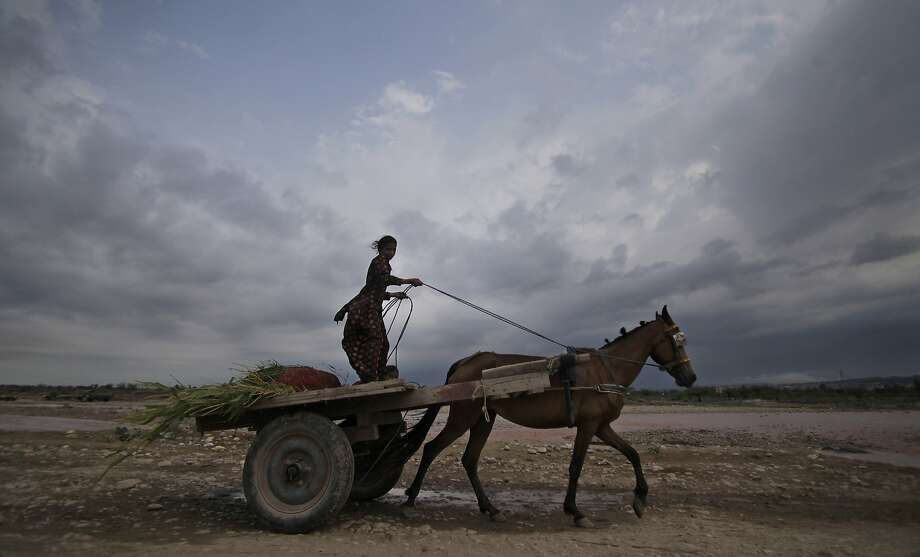 An Indian girl rides a horse cart as monsoon clouds hover in Jammu, India, Thursday, July 17, 2014. (AP Photo/Channi Anand) Photo: Channi Anand, Associated Press