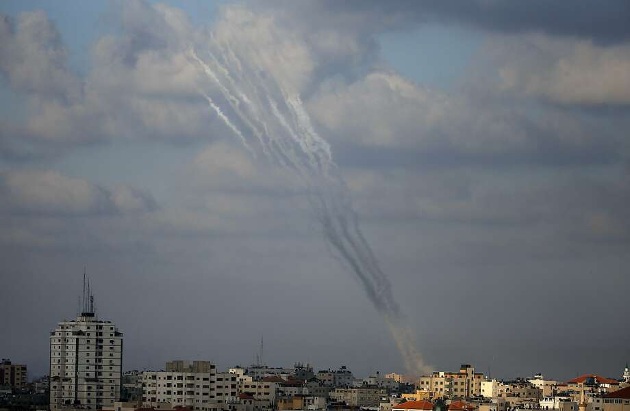 Smoke from rockets fired from a northern neighborhood of Gaza City are seen after being launched toward Israel on July 17, 2014. Israeli air strikes in Gaza killed four children, medics said, after a humanitarian lull in a 10-day conflict that has killed 237 Palestinians. AFP PHOTO / THOMAS COEXTHOMAS COEX/AFP/Getty Images Photo: Thomas Coex, AFP/Getty Images