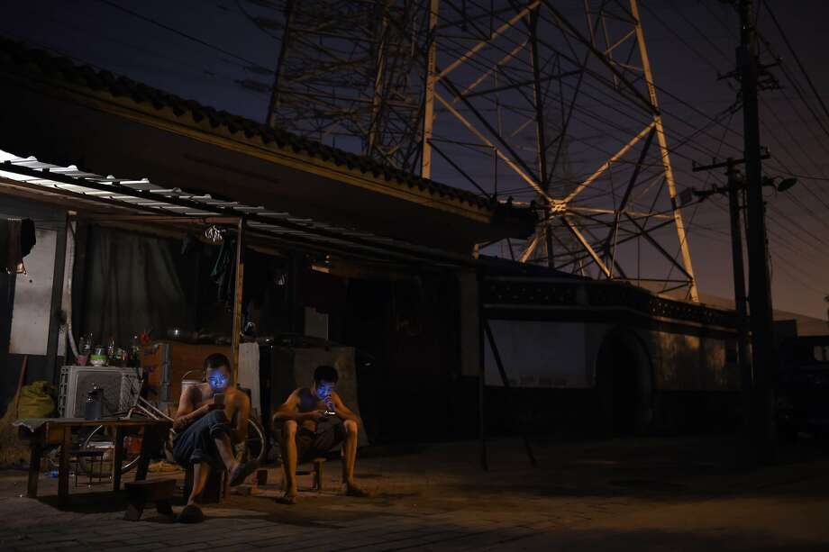 This photo taken on July 17, 2014 shows two men looking at smart phones outside an apartment below electricity pylons in Beijing.  Chinese growth accelerated to a forecast-beating 7.5 percent in the second quarter, official data showed on July 16, as government stimulus provided a much-needed boost to the world's second-largest economy. AFP PHOTO/Greg BAKERGREG BAKER/AFP/Getty Images Photo: Greg Baker, AFP/Getty Images