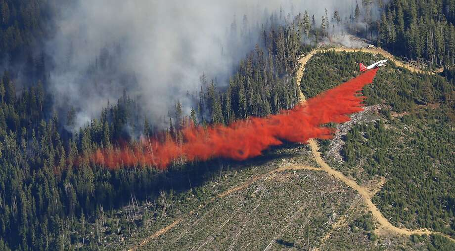 A plane drops fire retardant on the Chiwaukum Creek Fire near Leavenworth, Wash., Thursday, July 17, 2014. The blaze closed a section of U.S. Highway 2, and resulted in the evacuation of nearly 900 homes. (AP Photo/Ted S. Warren) Photo: Ted S. Warren, Associated Press