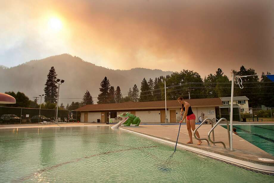 Jana Witkowski, a lifeguard at the Leavenworth, Wash. swimming pool, cleans ash and burned embers from the bottom of the pool that fell from the Chiwaukum Fire, Thursday, July 17, 2014. The pool was closed all day because of the amount of particles in the pool. (AP Photo/The Wenatchee World, Don Seabrook) Photo: Don Seabrook, Associated Press