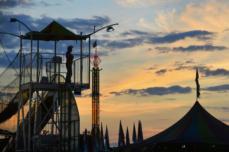 Amusement rides are silhouetted at sunset at the Heart of Illinois Fair in Peoria, Ill., on Thursday, July 17, 2014.(AP Photo/Peoria Journal Star/Ron Johnson) Photo: Ron Johnson, Associated Press