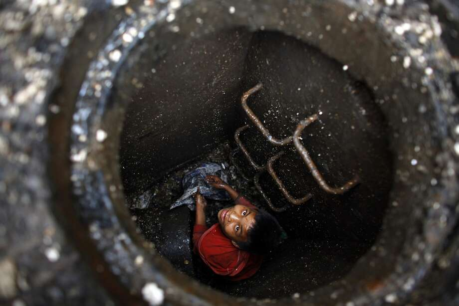 A young Nepalese boy manually clears a block in a sewer at the Kalimati vegetable market in Katmandu, Nepal, Thursday, July 17, 2014. Young children are commonly used as cheap labour to clean public toilets, clear blocked drains and clear garbage piling up in market areas. (AP Photo/Niranjan Shrestha) Photo: Niranjan Shrestha, Associated Press