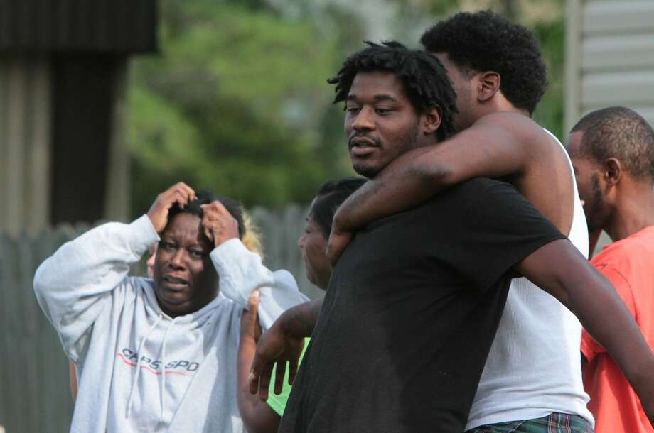 Jarmal Thompson, center, of Gulfport, Miss., is held by his cousin, Jacque Chambers, after they talked to police at a trailer on Whitney Drive in Gulfport where the body of Thompson's daughter, five-year-old Janaya Thompson, was found on Thursday July 17, 2014 in a vacant mobile home, and her death is being investigated as a homicide.The child had last been seen in the parking lot outside the apartment about 8:30 p.m. Wednesday.   (AP Photo/Sun Herald, John Fitzhugh) Photo: John Fitzhugh, Associated Press