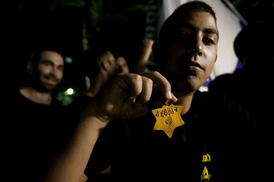 Israeli extreme right wing activist holds up a yellow Star of David with the Hebrew word Jew as he protests in support of the Israeli military operation in the Gaza Strip and against a left wing demonstration denouncing the offensive on July 17, 2014, in Jerusalem. Israeli tank fire in Gaza killed three people today night, raising the Palestinian death toll in 10 days of violence in the coastal enclave to 240, medics said. AFP PHOTO/GALI TIBBONGALI TIBBON/AFP/Getty Images Photo: Gali Tibbon, AFP/Getty Images