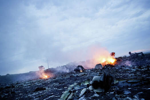Debris from Malaysia Airlines Flight 17 is shown smouldering in a field  July 17, 2014 in Grabovo, Ukraine near the Russian border. Flight 17, on its way from Amsterdam to Kuala Lumpur and carrying 295 passengers and crew, is believed to have been shot down by a surface-to-air missile, according to U.S. intelligence officials and Ukrainian authorities quoted in published reports. The area is under control of pro-Russian militias. Photo: Pierre Crom, Getty Images / 2014 Pierre Crom