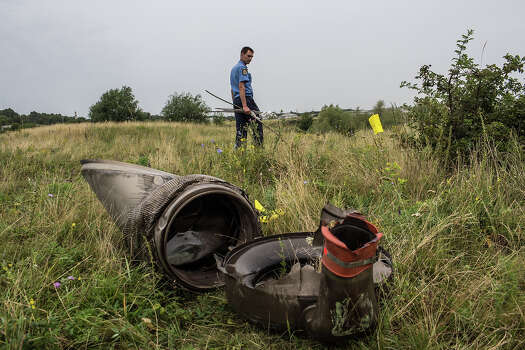 A Ukrainian police officer searches for human remains found in a field on July 18, 2014 in Grabovka, Ukraine. Air Malaysia flight MH17 traveling from Amsterdam to Kuala Lumpur crashed yesterday on the Ukraine/Russia border near the town of Shaktersk. The Boeing 777 was carrying 298 people including crew members, the majority of the passengers being Dutch nationals, believed to be at least 173, 44 Malaysians, 27 Australians, 12 Indonesians and 9 Britons. It has been speculated that the passenger aircraft was shot down by a surface to air missile by warring factions in the region. Photo: Brendan Hoffman, Getty Images / 2014 Getty Images