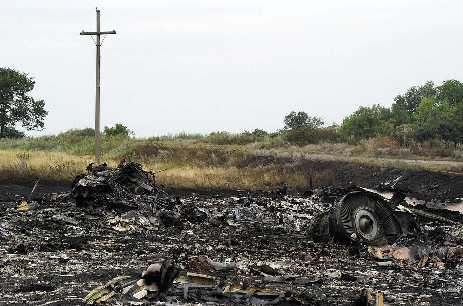 A picture taken on July 18, 2014 shows the wreckages of the Malaysia Airlines jet carrying 298 people from Amsterdam to Kuala Lumpur a day after it crashed, near the town of Shaktarsk, in rebel-held east Ukraine. Pro-Russian rebels fighting central Kiev authorities claimed on July 17 that the Malaysian airline that crashed in Ukraine had been shot down by a Ukrainian jet. The head of Ukraine's air traffic control agency said Thursday that the crew of the Malaysia Airlines jet that crashed in the separatist east had reported no problems during flight. All 298 people on board Flight MH17 died when the plane crashed. Photo: DOMINIQUE FAGET, AFP/Getty Images / AFP