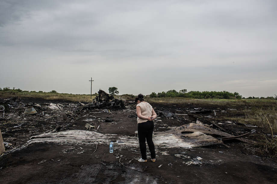 A woman looks at the wreckage of passenger plane Air Malaysia flight MH17 on July 18, 2014 in Grabovka, Ukraine. Air Malaysia flight MH17 travelling from Amsterdam to Kuala Lumpur crashed yesterday on the Ukraine/Russia border near the town of Shaktersk. The Boeing 777 was carrying 298 people including crew members, the majority of the passengers being Dutch nationals, believed to be at least 173, 44 Malaysians, 27 Australians, 12 Indonesians and 9 Britons. It has been speculated that the passenger aircraft was shot down by a surface to air missile by warring factions in the region. Photo: Brendan Hoffman, Getty Images / 2014 Getty Images