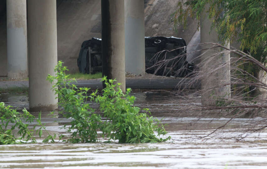 A car is on its side Friday July 18, 2014 near flooded Leon Creek at U.S. Highway 90 after torrential downpours swept through the San Antonio area last night.
