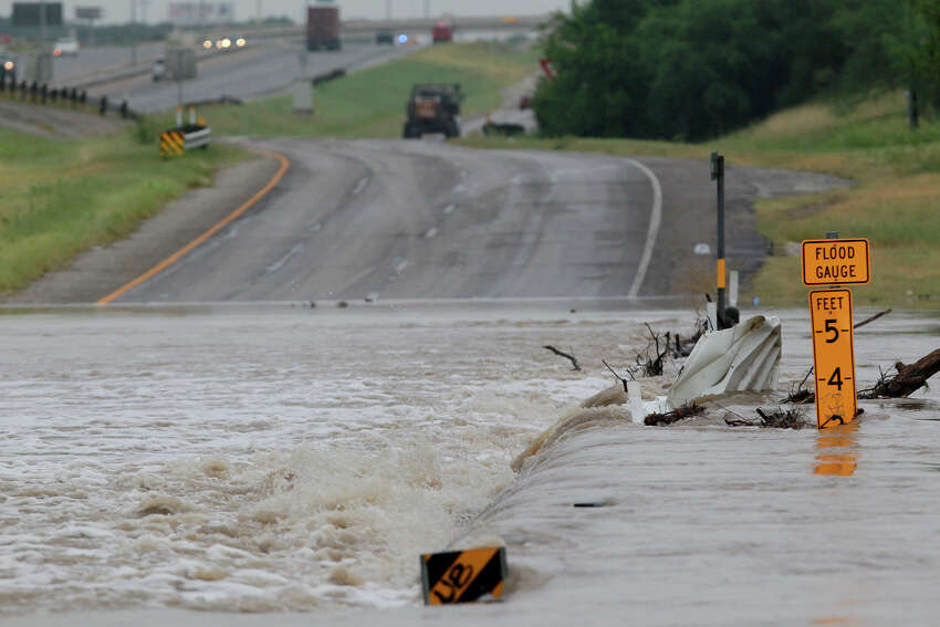 Leon Creek floods over the access road of U.S. Highway 90 west Friday July 18, 2014 after storms swept through San Antonio last night.