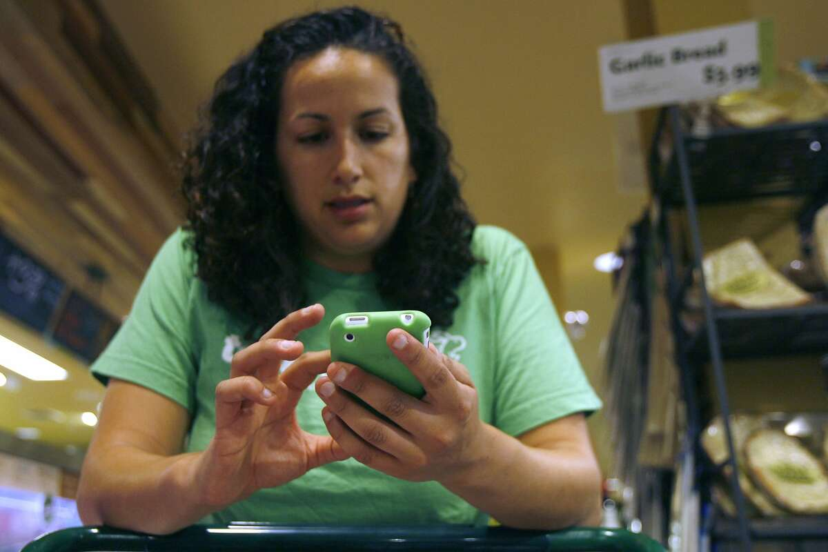 TaskRabbit employee Diane Barghouthy accesses a client's online grocery list from her phone while shopping at Whole Foods in Noe Valley, San Francisco, Calif. on Friday, Oct. 8, 2010. TaskRabbit started in Boston, Mass. and now has an office in San Francisco where clients can outsource their tasks to be done by someone else such as grocery shopping.