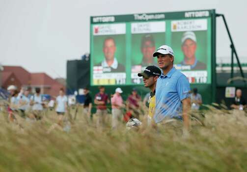 Robert Karlsson of Sweden and his caddie Dan Parratt walk along the 17th fairway during the second day of the British Open Golf championship at the Royal Liverpool golf club, Hoylake, England, Friday July 18, 2014. (AP Photo/Alastair Grant) Photo: Alastair Grant, Associated Press / AP
