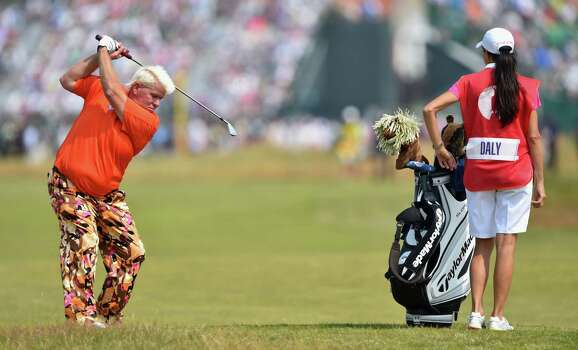 HOYLAKE, ENGLAND - JULY 18:  John Daly of the United States hits a shot on the 18th hole as his girlfriend/caddie Anna Cladakis looks on during the second round of The 143rd Open Championship at Royal Liverpool on July 18, 2014 in Hoylake, England. Photo: Stuart Franklin, Getty Images / 2014 Getty Images