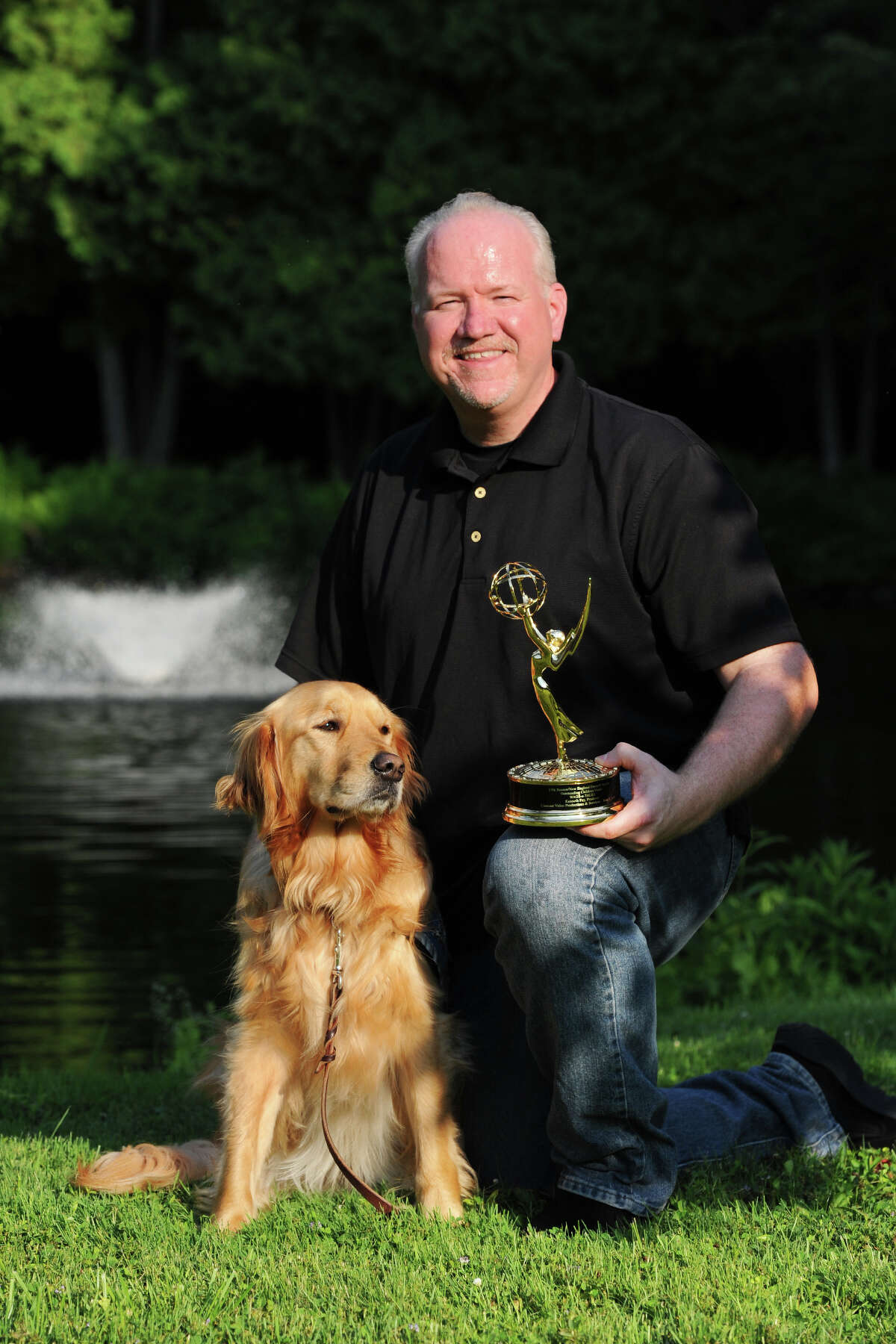 Ken Fay poses with comfort dog Maggie and his Emmy Award in Newtown, Conn. July 18, 2014. Fay recently received the Emmy for his film