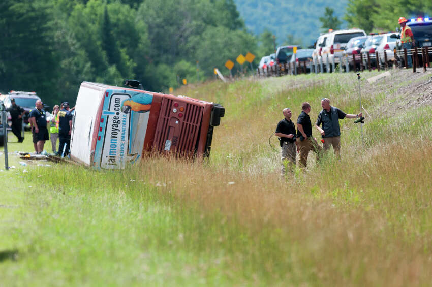 Emergency personnel investigate the scene of fatal bus crash near exit 29 of the Northway in the southbound lanes Friday morning, July 18, 2014, in North Hudson, N.Y. One person was killed and 55 injured. The bus was traveling from Quebec to New York City. (Tom Brenner/ Special to the Times Union)