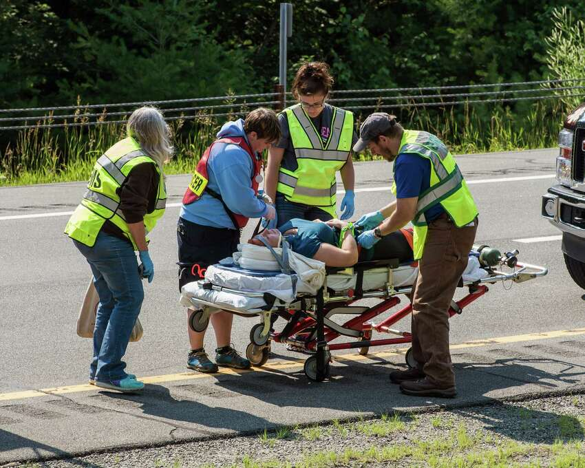Emergency personnel attend to a victim after a bus accident on Interstate 87, also known as the Adirondack Northway, in North Hudson, N.Y. on Friday July 18, 2014. Officials say a Canadian tour bus carrying more than 50 people rolled over, killing one and injuring others. The tour operator says the bus was traveling from Quebec City to New York City. Josiane Grimard of JaimonVoyage.com says the bus crashed at 7:30 a.m. She had no word on the cause. She said the vehicle was owned by a subcontractor. (AP Photo/John DiGiacomo) ORG XMIT: NYJD104