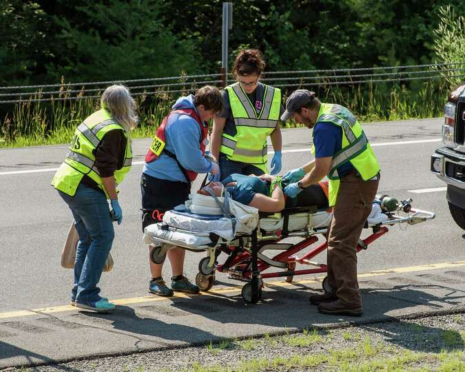 Emergency personnel attend to a victim after a bus accident on Interstate 87, also known as the Adir