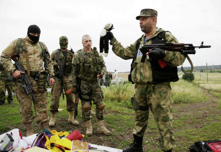 A pro-Russian fighter holds up a toy found among the debris at the crash site of a Malaysia Airlines jet near the village of Hrabove, Friday, July 18, 2014. Emergency workers, police officers and even off-duty coal miners spread out Friday across the sunflower fields and villages of eastern Ukraine, searching the wreckage of a Malaysia Airlines jet shot down as it flew high above the country's battlefield. The attack Thursday afternoon killed 298 people from nearly a dozen nations. Photo: Dmitry Lovetsky, Wire Photos / AP2014