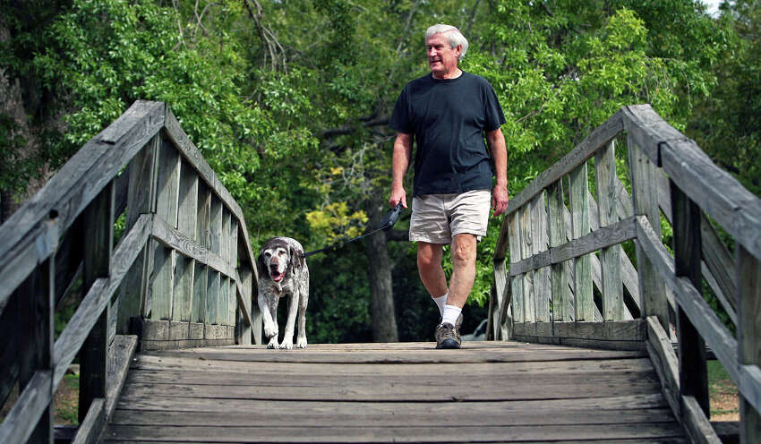 Cool dry air at Landa Park in New Braunfels provide Kermit Doerr and his dog Sedgewick a pleasant outing as they walk over a footbridge in the park. Sedgewick, a German short haired pointer, is a retired showdog.
